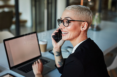 Buy stock photo Shot of an attractive young businesswoman taking a phone call while working late in her office