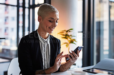 Buy stock photo Shot of an attractive young businesswoman using her cellphone while working late in her office