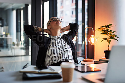 Buy stock photo Shot of an attractive young businesswoman relaxing with her hands behind her head while working late in her office