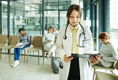 Buy stock photo Shot of a confident young doctor standing in the waiting room of a clinic