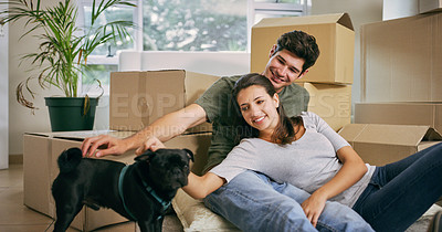 Buy stock photo Shot of a couple spending time with their dog in their new home