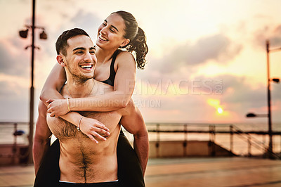 Buy stock photo Shot of two sporty young people having fun while exercising together outdoors