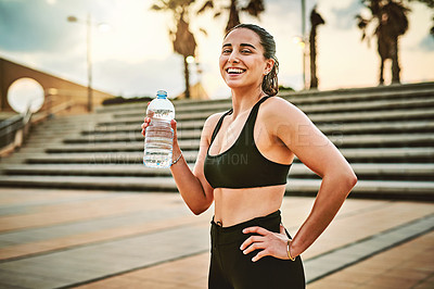 Buy stock photo Portrait of a sporty young woman drinking water while exercising outdoors