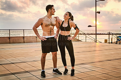 Buy stock photo Shot of two sporty young people taking a break while exercising together outdoors