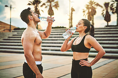 Buy stock photo Shot of two sporty young people drinking water while exercising outdoors