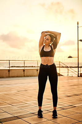 Buy stock photo Shot of a sporty young woman stretching while exercising outdoors