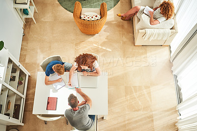 Buy stock photo High angle shot of a father assisting his two children with their homework while his wife relaxes in the lounge