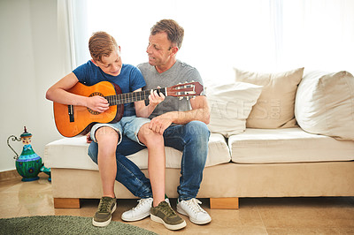 Buy stock photo Full length shot of a father teaching his son how to play the guitar at home