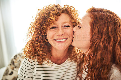 Buy stock photo Shot of a mother getting a kiss on the cheek from her teenage daughter at home