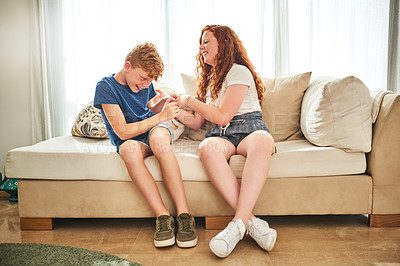 Buy stock photo Full length shot of a cheerful teenage brother and sister playing together while sitting on a couch at home