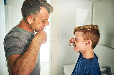 Buy stock photo Shot of a father and son brushing their teeth in the bathroom at home