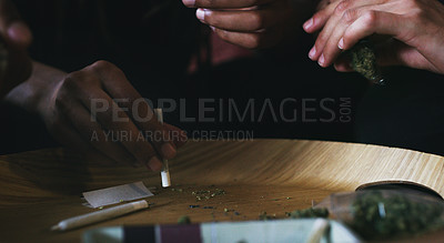 Buy stock photo Cropped shot of men rolling a marijuana joint at home
