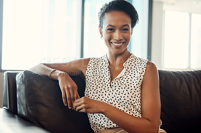 Buy stock photo Portrait of an attractive young businesswoman sitting on a couch in her office