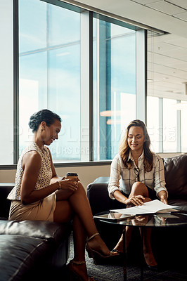 Buy stock photo Full length shot of two young businesswomen using a digital tablet while going over some paperwork in their office