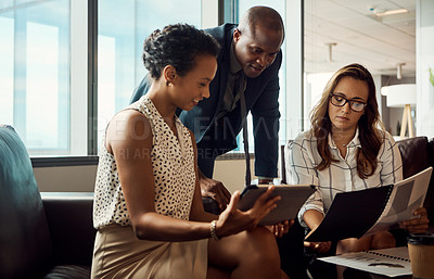 Buy stock photo Shot of a group of businesspeople using a digital tablet while going over some paperwork in their office