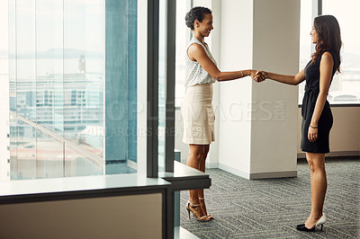 Buy stock photo Full length shot of two attractive young businesswomen shaking hands in an office