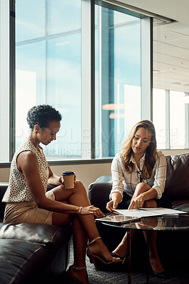 Buy stock photo Full length shot of two young businesswomen going over some paperwork together in their office