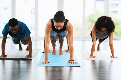 Buy stock photo Shot of a group of young people practicing yoga together inside a studio