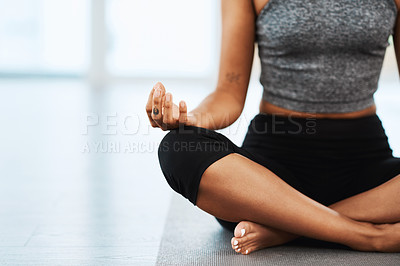 Buy stock photo Shot of an unrecognizable woman sitting down and meditating while practicing yoga inside a studio