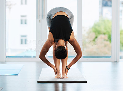 Buy stock photo Full length shot of an attractive young woman practicing yoga inside a studio