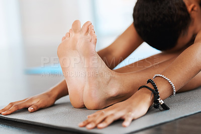 Buy stock photo Shot of a young woman doing her stretches while practicing yoga inside a studio
