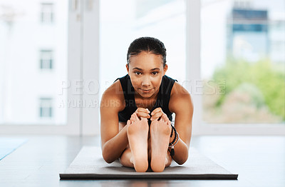 Buy stock photo Portrait of an attractive young woman sitting down and doing her stretches while practicing yoga inside a studio