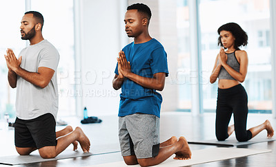 Buy stock photo Full length shot of a group of young people meditating and practicing yoga together inside a studio