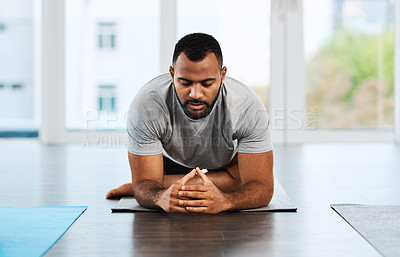Buy stock photo Shot of a handsome young man practicing yoga inside a studio