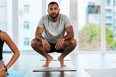 Buy stock photo Full length shot of a handsome young man practicing yoga inside a studio