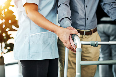 Buy stock photo Cropped shot of a nurse helping a senior man with a walker