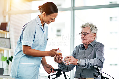 Buy stock photo Shot of a young nurse giving a senior man his medication to take with a glass of water