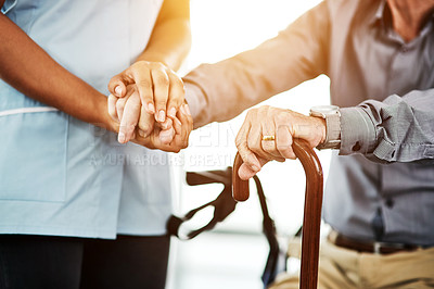 Buy stock photo Cropped shot of a nurse holding hands with a senior man using a cane