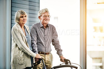 Buy stock photo Shot of a senior woman helping her husband with a walker
