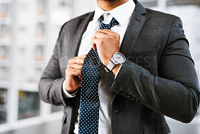 Buy stock photo Closeup shot of a businessman adjusting his tie in an office