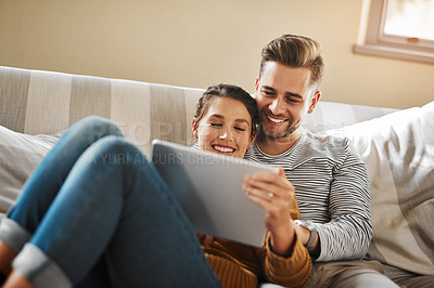 Buy stock photo Shot of a young couple using a digital tablet while relaxing at home