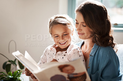 Buy stock photo Shot of an adorable little girl reading a book together with her mother on the sofa at home