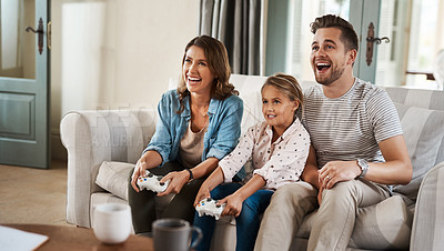 Buy stock photo Shot of a happy young family playing video games on the sofa at home