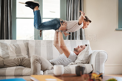 Buy stock photo Shot of an adorable young boy and his father playing together on the sofa at home