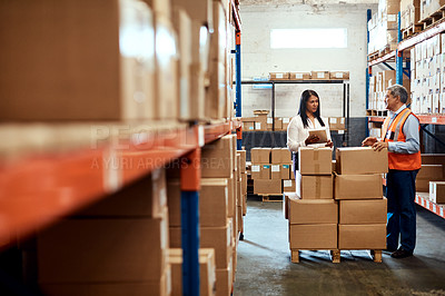 Buy stock photo Shot of a mature man and woman using a digital tablet while working together in a warehouse