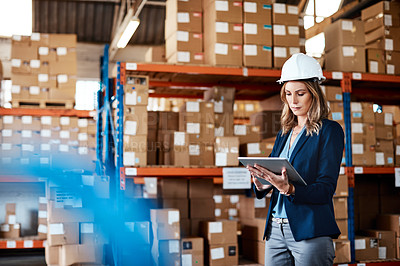 Buy stock photo Shot of a young woman using a digital tablet while working in a warehouse