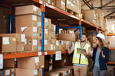 Buy stock photo Cropped shot of an attractive young businesswoman walking through a warehouse with a male worker