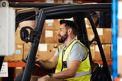 Buy stock photo Cropped shot of a handsome young male warehouse worker driving a forklift