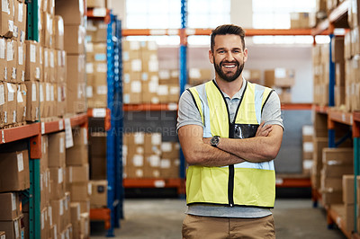 Buy stock photo Cropped portrait of a handsome young male warehouse worker standing with his arms crossed