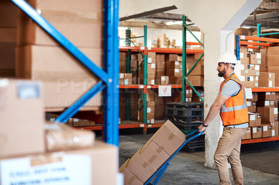 Buy stock photo Shot of a young man moving boxes on a trolley in a warehouse