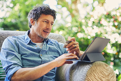 Buy stock photo Shot of a mature man relaxing in a chair while using a digital tablet and credit card in his backyard