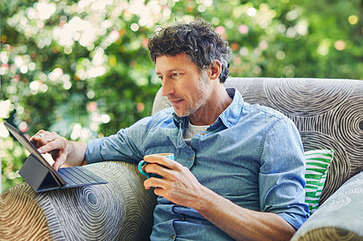 Buy stock photo Shot of a mature man relaxing in a chair while using a digital tablet and drinking coffee in his backyard