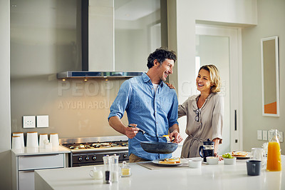 Buy stock photo Shot of a mature man preparing breakfast for him and his wife at home