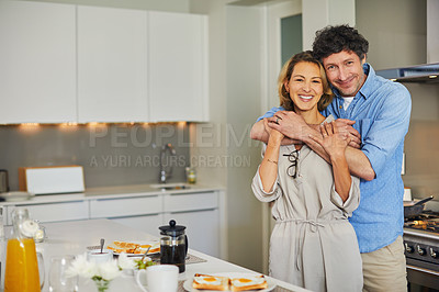 Buy stock photo Shot of a mature couple hugging while preparing breakfast together at home