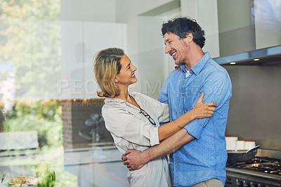 Buy stock photo Shot of a mature couple hugging in the kitchen at home