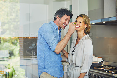 Buy stock photo Shot of a mature man giving his wife a taste of his cooking at home